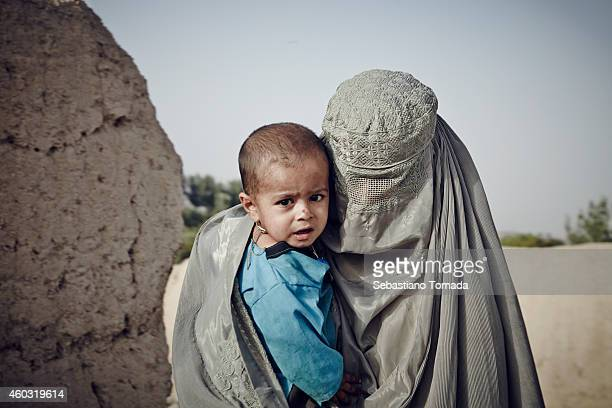 A woman wearing a traditional burka carries her child through the street of a small village in Arghandab valley The International Security Assistance...