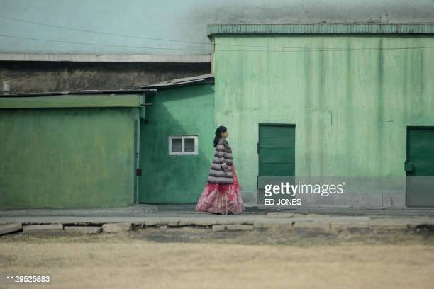 Woman wearing a traditional dress walks along a street during voting for the Supreme People's Assembly elections, in Pyongyang on March 10, 2019. -...