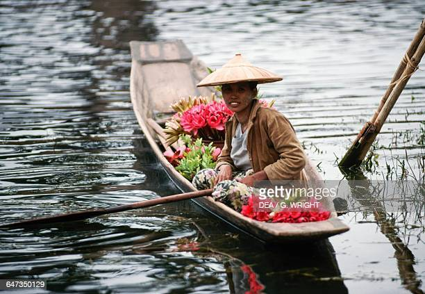 Woman wearing a traditional hat transpoting flowers in a pirogue Ywama Burma
