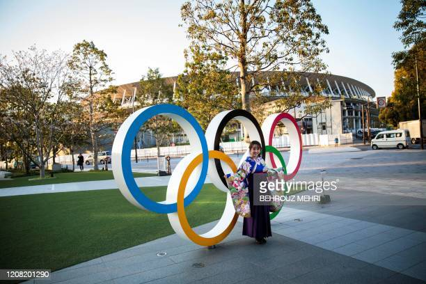 A woman wearing a traditional Japanese kimono poses next to the Olympic rings in front of the Japan National Stadium the main venue for the Tokyo...
