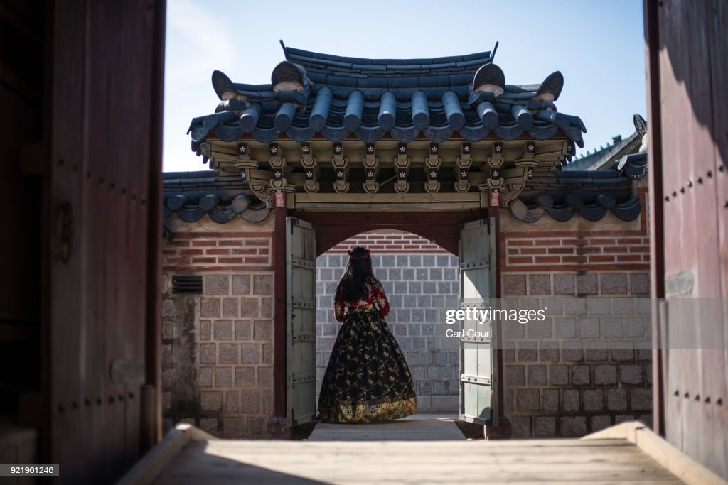 A woman wearing a traditional Korean Hanbok dress poses for a photograph in a doorway as she visits Gyeongbokgung Palace on February 21, 2018 in Seoul, South Korea. With tourists visiting from around the world, leaders from South Korea's capital as well as GyeongGi and Gangwon Provinces have agreed to work together to support the PyeongChang Olympic Games and to invigorate regional tourism.