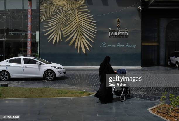 A woman wearing a traditional niqab and black abaya pushes a child stroller outside an upscale shopping center on June 20 2018 in Riyadh Saudi Arabia...