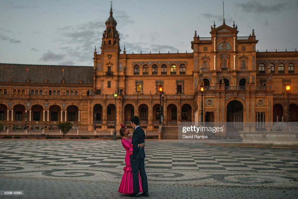 A woman wearing a traditional Sevillana dress hugs her boyfriend at Plaza de Espana (Spain's Square) during the Feria de Abril (April's Fair) on April 12, 2016 in Seville, Spain. The Feria de Abril has a history that dates back to 1857 and takes place a fortnight after Easter each year. The origin of the fair was a cattle market but the event quickly turned its goal from commerce to having fun. More than 1 million local and international participants are expected to attend the Feria de Abril.
