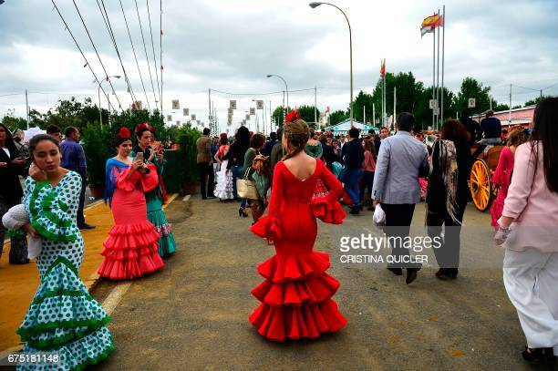 A woman wearing a traditional Sevillian dress poses for a photo during the 'Feria de Abril' in Sevilla on April 30 2017 The fair dates back to 1847...