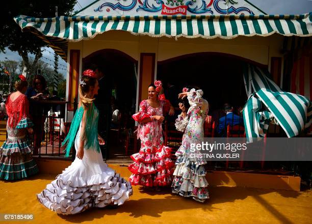 A woman wearing a traditional Sevillian dress poses for a picture during the Feria de Abril in Sevilla on April 30 2017 The fair dates back to 1847...