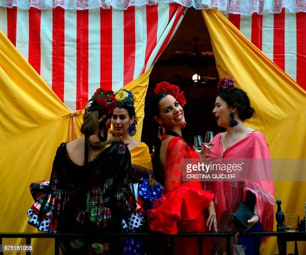 A woman wearing a traditional Sevillian dress smiles as she drinks Fino wine with friends during the Feria de Abril in Sevilla on April 30 2017 The...