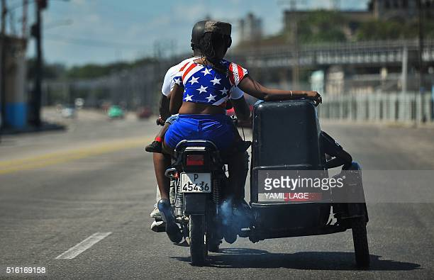TOPSHOT A woman wearing a tshirt in the colours of the US flag rides a motorcycle in Havana on March 17 2016 Hundreds of workers have been scrambling...