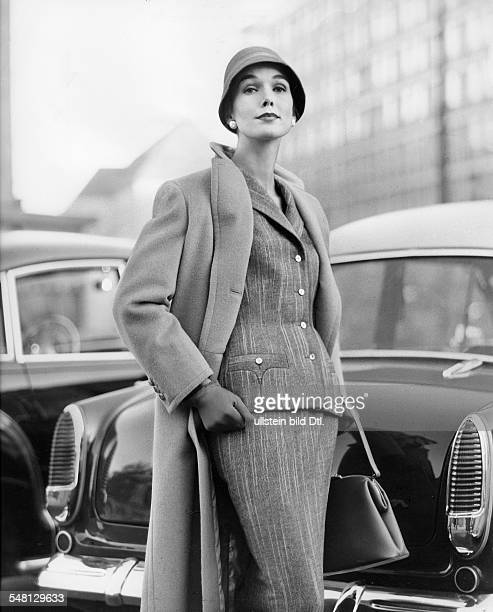 Woman wearing a tweed costume comprising a fitted jacket and narrow skirt as well as a camel hair coat and narrow felt hat model 'Chic' and coat...