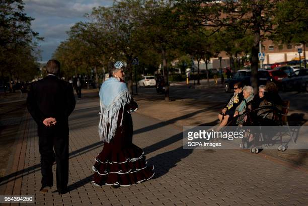 A woman wearing a typical flamenco dress seen walking with her husband El día de la Cruz or Día de las Cruces is one of the most beautiful...