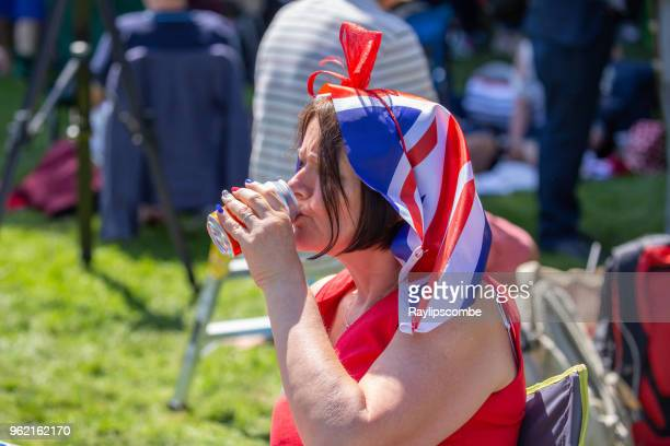 Woman wearing a union jack headscarf relaxing with a drink amongst the crowds of people lining Windsor Great Park's 'Long Walk' to celebrate the marriage of Meghan Markle and Prince Harry