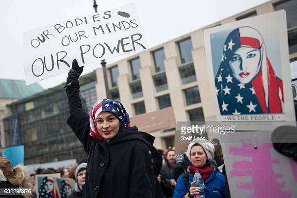Woman wearing a USA flag as a headscarf attends a protest for women's rights and freedom in solidarity with the Women's March on Washington in front...