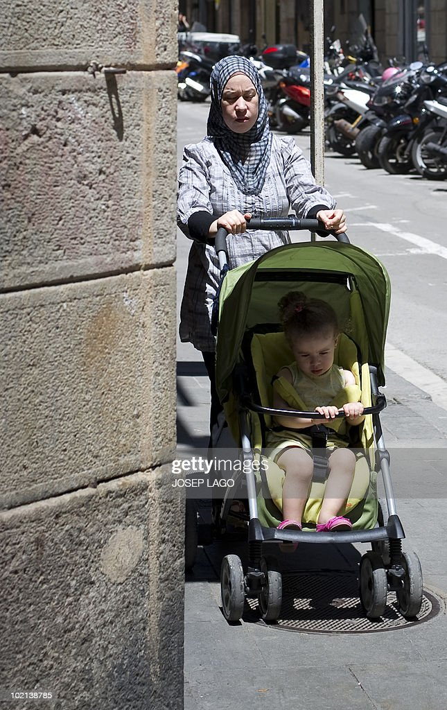 A woman wearing a veil pushes a pushchair in Barcelona on June 16, 2010. Spain's government plans to ban the use of the Islamic burqa in public places under a proposed new law on religious freedom, the justice minister said on June 15, 2010. His remarks came a day after the mayor of Barcelona, Jordi Hereu, announced it would be the first large city in Spain to ban the use of the full-face Islamic veil in public buildings. Immigration from Muslim countries has soared in Spain since the 1990s, with Catalonia in particular being home to a large community of Pakistani origin.