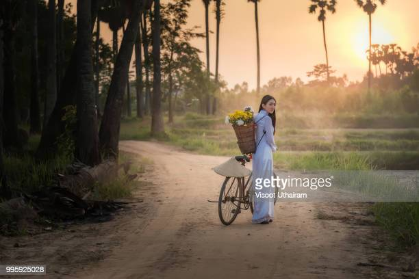 Woman wearing a Vietnamese dress Ao Dai are ride on a bicycle along the road in a village