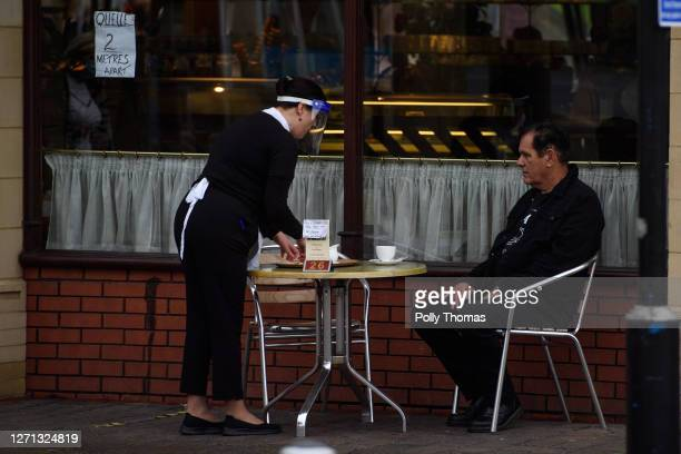 Woman wearing a visor serves a man outside a cafe on September 08, 2020 in Caerphilly, United Kingdom. The county borough of Caerphilly in South...