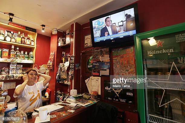 Woman wearing a 'Vote Yes' shirt, written in Spanish, watches a news broadcast as results come in from the referendum on a peace accord to end the...