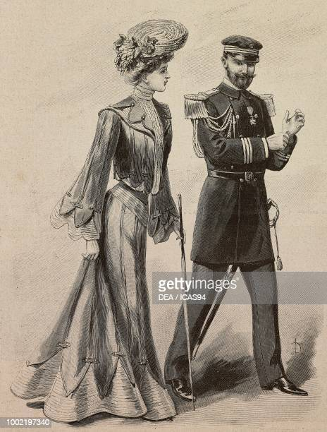 Woman wearing a walking dress flared skirt blouse with wide sleeves straw hat with flowers creation by Madame LimousinBonnefoy man wearing a second...