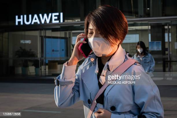 Woman wearing a wearing a facemask as a preventive measure against the COVID-19 coronavirus speaks on her smartphone outside a shopping mall past a...