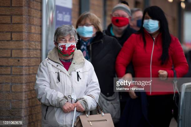 Woman wearing a Welsh flag face mask stands in a queue for the Pfizer-BioNTech COVID-19 vaccine at Cardiff and Vale Therapy centre on Splott Road on...