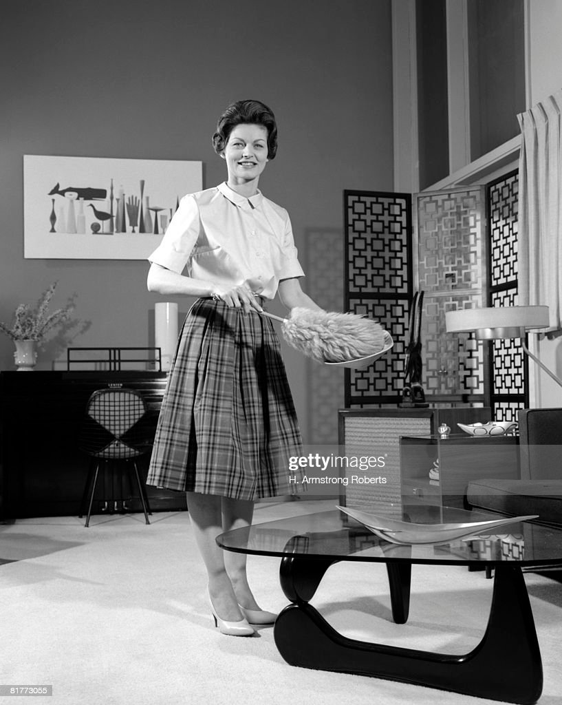 Woman Wearing A White Blouse & Plaid Skirt Dusting A Bowl With A Feather Duster In Front Of A Glass Top Coffee Table Smiling Modern Living Room. : Foto de stock