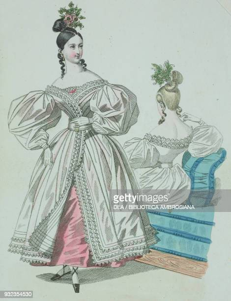 Woman wearing a white dress with puffed sleeves lacework trim over a pink dress with roses in her hair and a woman wearing the same outfit seated in...