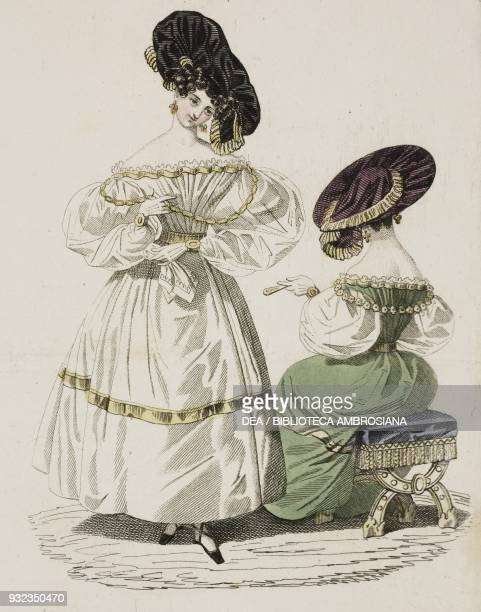 Woman wearing a white dress with puffed sleeves large black hat with gold trim and a woman wearing the same dress and hat in green seated in the...
