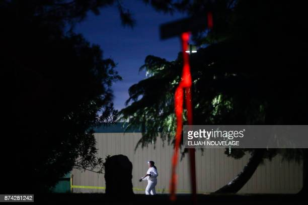 A woman wearing a white protective suit is seen on the Rancho Tehama Elementary school grounds after a shooting on November 14 in Rancho Tehama...