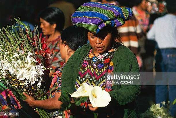Woman wearing a woollen hat and holding a calla lily in her hand at the flower market Chichicastenango Quiche Guatemala