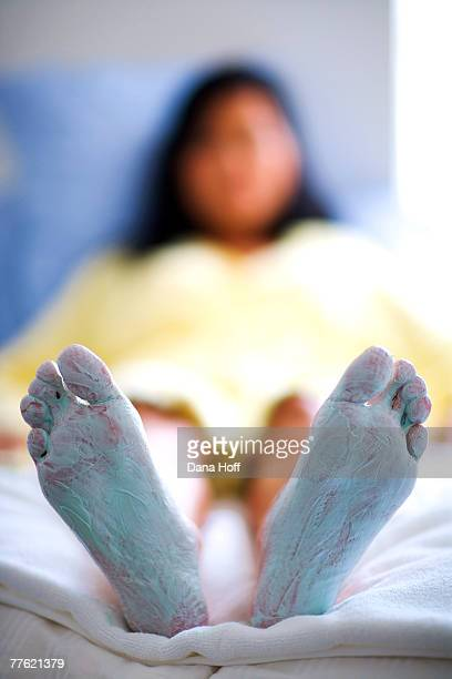a woman wearing a yellow bathrobe relaxes in her bed with cream applied to her feet - frau gespreizte beine stock-fotos und bilder