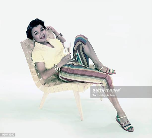 A woman wearing a yellow blouse striped pants and sandals reclines an a woven chair while holding a glass of beer 1953