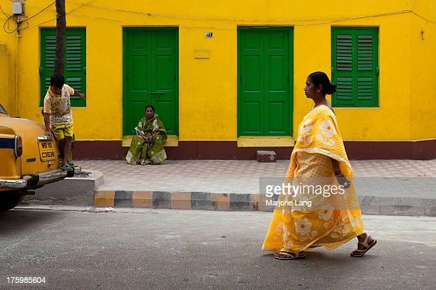 CONTENT] Woman wearing a yellow sari walking by a colorful yellow and green building with a woman in a green sari sitting at the door and a child in...