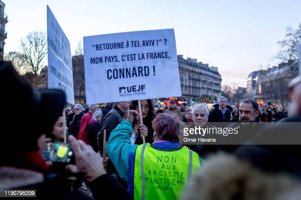 A woman wearing a yellow vest on which are written antiracism slogans argues with another woman about the message of the sign she is holding during...