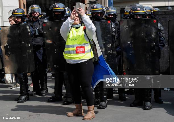 A woman wearing a yellow vest takes a selfie picture with riot police officers prior to the start of May Day demonstrations in Paris on May 1 2019...