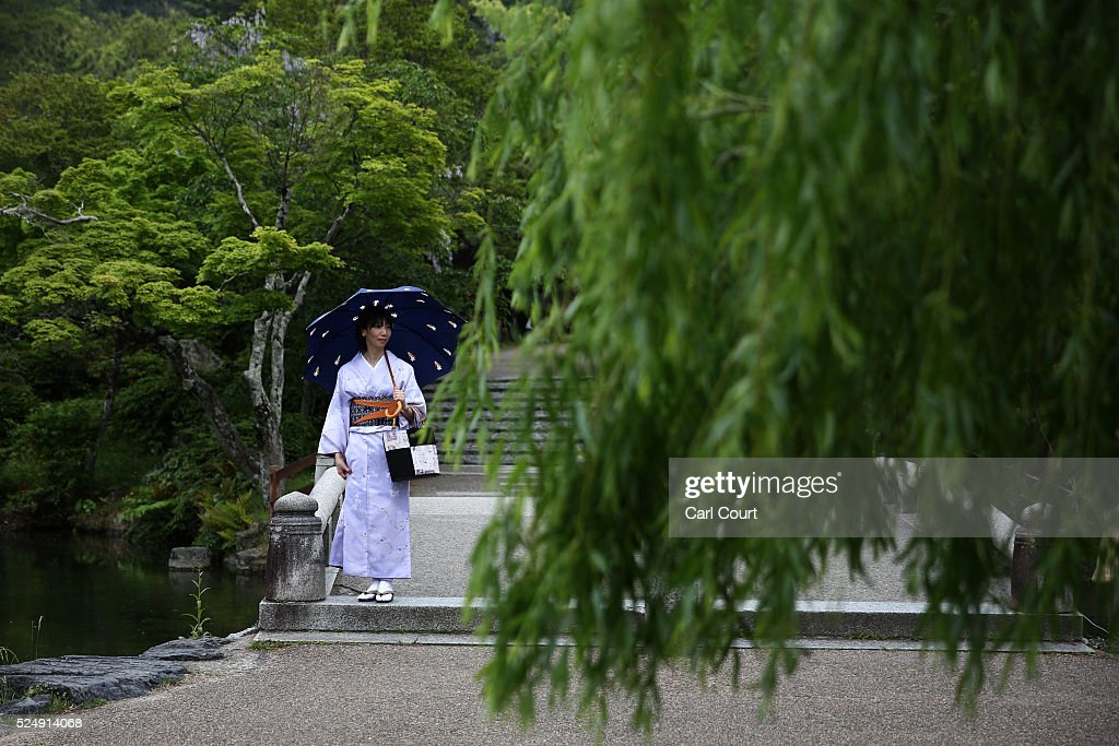 A woman wearing a yukata, a light, unlined, summer kimono made of cotton instead of the traditional silk, walks through a park on April 27, 2016 in Kyoto, Japan. Now the seventh largest city in Japan, Kyoto was once the Imperial capital for more than one thousand years, it is now the capital city of Kyoto Prefecture and a major part of the Kyoto-Osaka-Kobe metropolitan area.