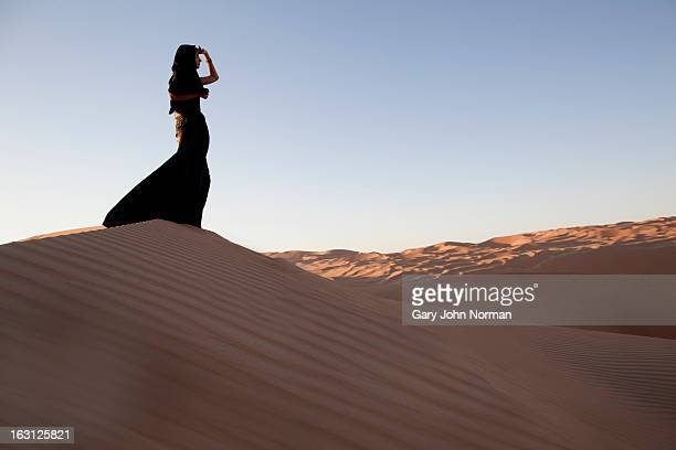 Woman wearing Abaya in desert at Liwa Oasis, UAE