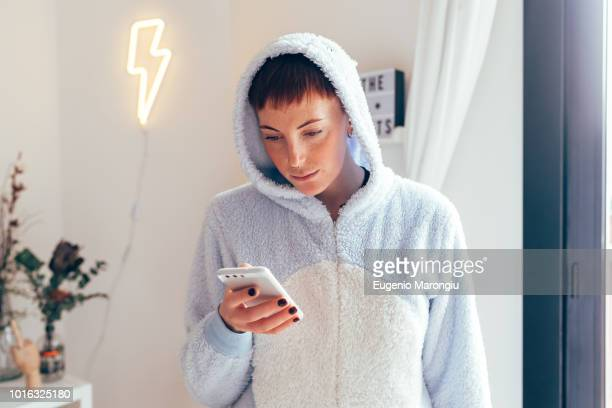 woman wearing adult bodysuit texting on smartphone - bodysuit stock pictures, royalty-free photos & images