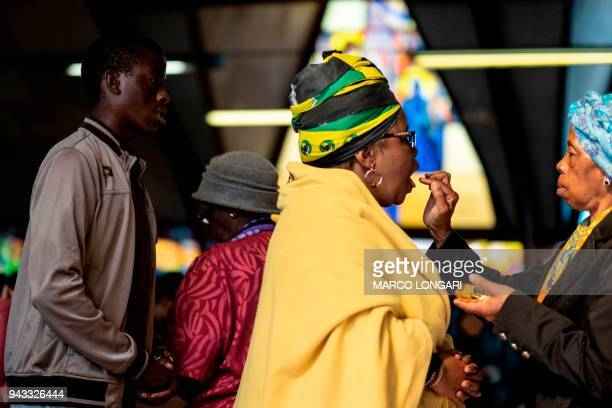 A woman wearing African National Congress regalia receives the communion during the Sunday service at the iconic Regina Mundi Church in Soweto near...