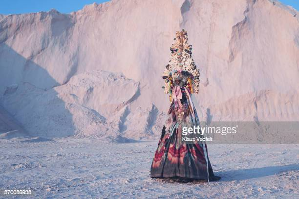 Woman wearing amazing costume, standing in limestone landscape