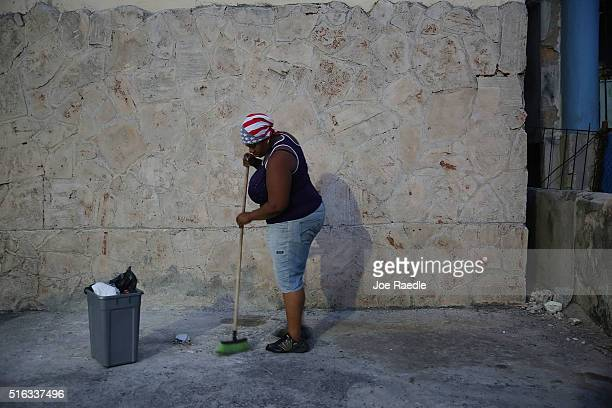 Woman wearing an American flag head scarf sweeps in front of her store as Cuba prepares for the visit of U.S. President Barack Obama on March 18,...