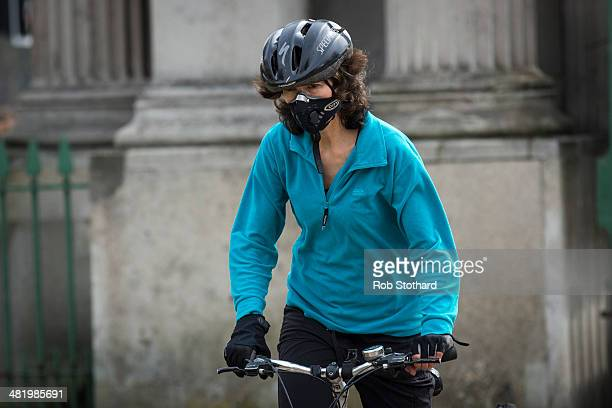 A woman wearing an antipollution mask rides a bicycle at Hyde Park Corner on April 2 2014 in London England Dust from the Sahara combined with...
