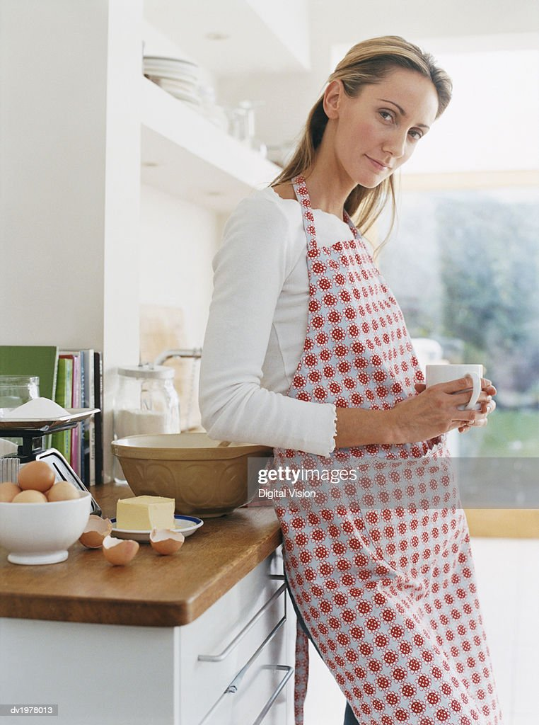 Woman Wearing an Apron Leans Against a Kitchen Counter Holding a Cup : Stock Photo