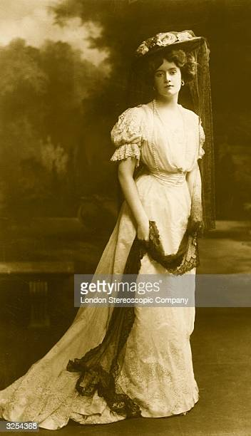 Woman wearing an Edwardian dress and hat with a lace veil.