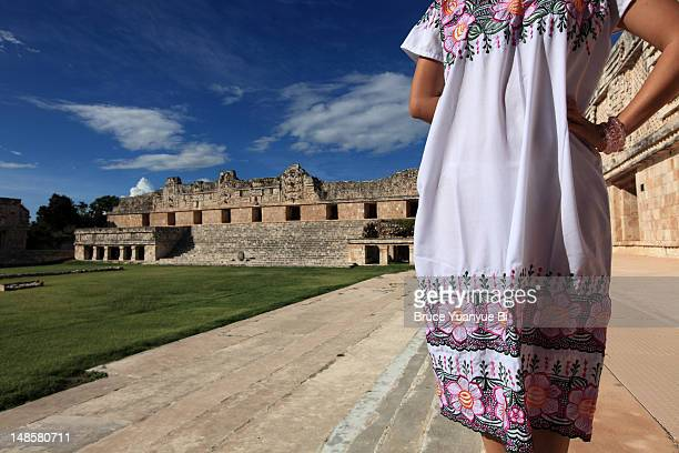 Woman wearing an embroidered Mexican dress at Nunnery Quadrangle (Cuadrangulo de las Monjas).