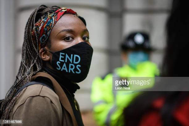 "Woman wearing an ""END SARS"" protective face mask speaks with the police outside the Nigerian Consulate during a demonstration on October 21, 2020 in..."