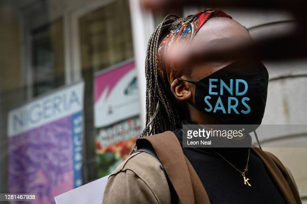 """Woman wearing an """"END SARS"""" protective face mask speaks with the police outside the Nigerian Consulate during a demonstration on October 21, 2020 in..."""