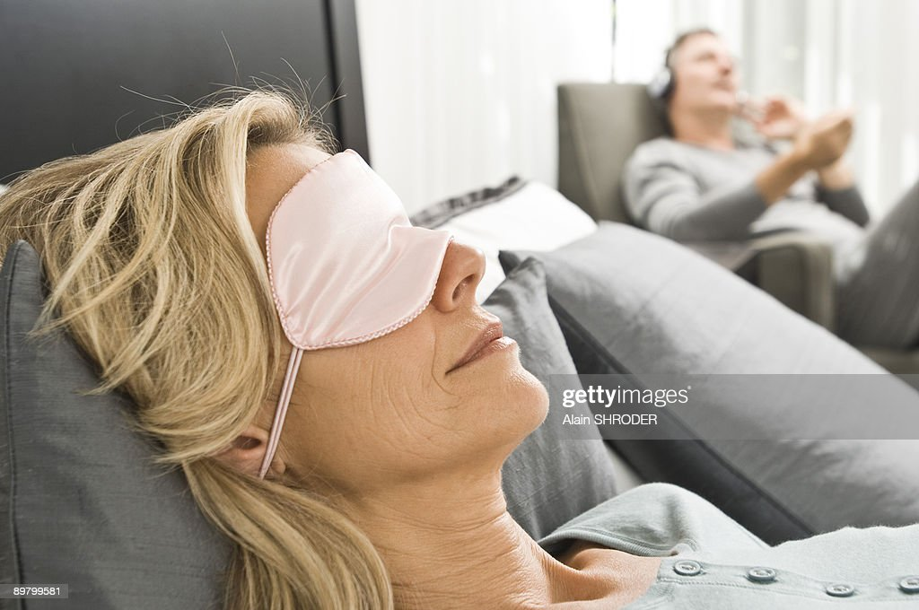 Woman wearing an eye mask and her husband listening to music in the background : Stock-Foto