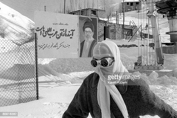Woman wearing an Islamic veil and skiing glasses, walks past a ski federation board in Shemshak, with a message by Ayatollah Ali Khamenei which reads...