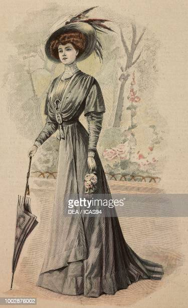 Woman wearing an opal coloured Crepe de Chine city dress crossover skirt on front pleated corset on front and a hat with feathers creation by Martial...
