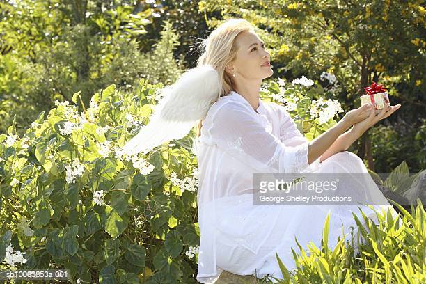 Woman wearing angel wings holding small gift, sitting in garden, side view