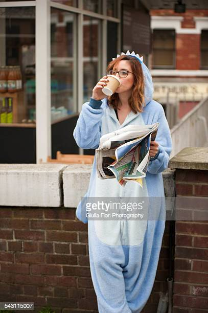 Woman wearing animal onesie drinking coffee