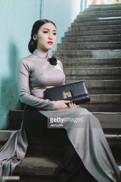 Woman wearing Aodai sitting in stair at ancient town, China Town, Saigon